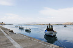 Fishing boats anchored at the dock. Small fishing boats anchored at the dock on very calm water royalty free stock photo