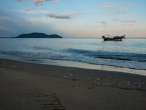 Fishing boats anchoring on the sea near by beach in sunset. With beach foreground at south of Thailand Stock Photo