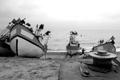 Fishing boats ashore. Three fishing boat standing on the beach, dreary winter weather, a pulling mechanism in the foreground. The Baltic Sea Stock Photography