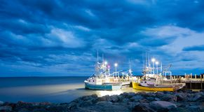 Fishing boats in the Bay of Fundy. Fishing boats moored in Alma, Bay of Fundy, on the New Bruswick Atlantic coastline in Canada. Blue hour shot with dramatic Royalty Free Stock Photos