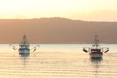 Fishing boats in bay at sunrise Stock Image