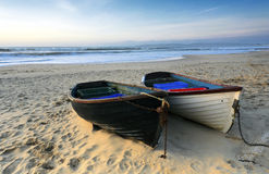 Fishing Boats on the Beach. Fishing boats on a sandy beach in Bournemouth with Old harry rocks and the Isle of Purbeck in the distance Stock Photos