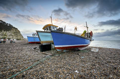 Fishing boats on the beach at Beer in Devon. Fishing boats at sunrise on the beach at Beer on Devon's Jurassic Coast Royalty Free Stock Image