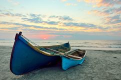 Fishing boats on the beach at sunrise Stock Images