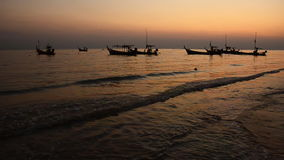 Fishing boats at the beach and sunset stock footage