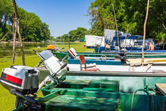 Fishing boats beached on overgrown river with duckweed. Royalty Free Stock Image