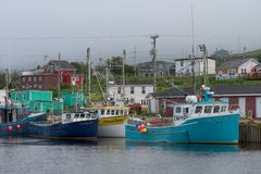 Fishing boats in Branch Harbour. Fishing boats in foggy harbor in Branch, Newfoundland and Labrador royalty free stock image