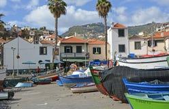 Fishing boats at Camara de Lobos, Madeira, Portugal. Fishing boats drawn up on beach and slipway at Camara de Lobos in Madeira, Portugal. With people in Royalty Free Stock Image