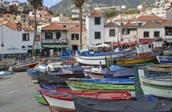 Fishing boats at Camara de Lobos, Madeira, Portugal. Fishing boats drawn up on beach and slipway at Camara de Lobos in Madeira, Portugal. With people in Royalty Free Stock Images
