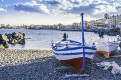 Fishing boats on the coast of the city of giardini naxos sicily. Sicilian coast at the height of the city of giardini naxos seen in the background and fishing Stock Image