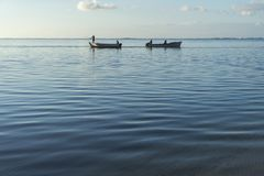 Fishing boats that cross at dawn with the calm sea stock photo
