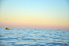 Fishing boats depart in the morning, during sunrise, in the sea Royalty Free Stock Image