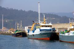 Trawler and longliners fishing boats docked in Celeiro harbor in Spain. Fishing boats docked in the fishing harbor of Celeiro after work all night in the coasts Royalty Free Stock Images