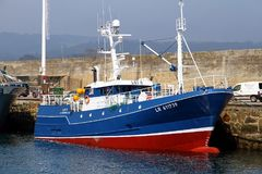 Trawler and longliners fishing boats docked in Celeiro harbor in Spain. Fishing boats docked in the fishing harbor of Celeiro after work all night in the coasts Stock Images