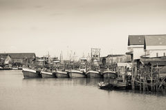 Fishing boats docked in sepia. Royalty Free Stock Photography