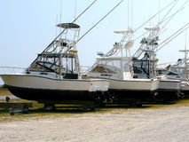 Fishing boats in drydock. A group of fishing boats sitting in a row in drydock at the harbor in the Outer Banks of North Carolina Stock Image