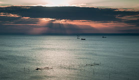 Fishing boats in the evening. Fishing boats out at sea in the in the evening in the background and fishing nets in the foreground Stock Photography