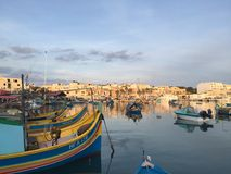 Fishing boats in the Fishing Village, Malta. Darkening skies at the fishing boats take rest in the calming Stock Images