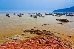 Fishing Boats Fleet At Noon. Fishing boats fleet anchored at sea of the shore of Kampung Pulau Sayak, Kedah, Malaysia with natural rock formation in the Royalty Free Stock Photo