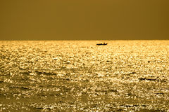 Fishing boats floating in the sea. Fishing boats floating in the sea with the golden light of the morning sun Stock Photos