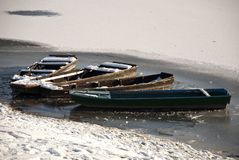 Fishing boats on frozen water Stock Images