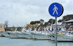 Fishing boats in the harbor dock. Cvitavecchia rome italy:some fishing boats in the harbor waiting to get out for a fishing tackle with a pedestrian access road Royalty Free Stock Photos