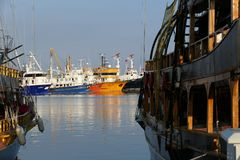 Fishing boats in a harbor. With one old pirate ship on the right side Stock Photo