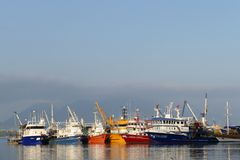 Fishing boats in a harbor. Fishing boats and ships in a harbor, reflection in the deep blue sea water Royalty Free Stock Photography