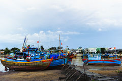 Fishing boats in harbor with the jetty at foreground Stock Images