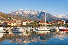 Fishing boats in harbor. Marina Kalimanj  in Tivat town on a winter day with Lovcen mountain in the background, Montenegro Stock Photo