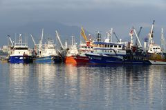 Fishing boats in a harbor. Reflection in the deep blue sea water royalty free stock photography