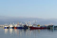 Fishing boats in a harbor. Fishing boats and ships in a harbor, reflection in the deep blue sea water Royalty Free Stock Image