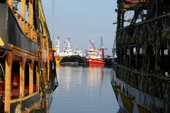 Fishing boats in a harbor. Between two old pirate ships, reflecting in the water Stock Photos