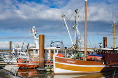 Fishing Boats in a Harbour and a Blue Sky. Norddeich, Germany - March 26, 2016: Fishing Boats in a Harbour and a Blue Sky Stock Images