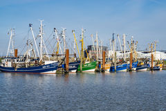 Fishing Boats in a Harbour and a Blue Sky. Norddeich, Germany - March 26, 2016: Fishing Boats in a Harbour and a Blue Sky Royalty Free Stock Photography