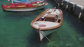 Fishing boats in harbour on a Greek Island. Old Greek wooden colorful anchored fishing boats swaying in a port in clear turquoise sea stock video footage