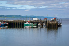 Fishing boats in the harbour at low tide in Digby, Nova Scotia. Nova Scotia late spring afternoon with evening approaching.   Boats tied up in low tide, in for Royalty Free Stock Image