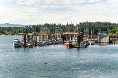 Fishing Boats in Harbour on a Summer Morning. Photo of a Fishing Harbour with Colourful Boats Tied up to Jetties on a Cloudy Summer Morning. Sooke, BC, Canada Stock Photography