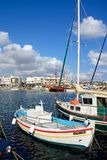 Fishing boats in Hersonissos harbour. Traditional fishing boats in the harbour with waterfront restaurants to the rear, Hersonissos, Crete, Europe Royalty Free Stock Photo