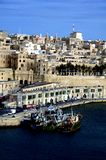 Fishing Boats and houses in Valletta,Malta. Vertical Photo of fishing boats and traditional stone made building in Valletta,Malta Stock Image