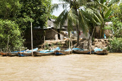 Fishing boats and huts along Mekong River. Picture of fishermen's boats and huts parked along muddy Mekong river royalty free stock photo