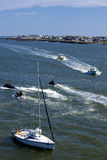 Fishing boats, jetskis and sailboat Stock Photo