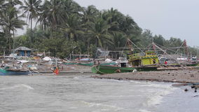 Fishing boats laying next the the Malandog beach in Philippines. Boats laying next to the beach during bad weather on Panay island in the Philippines stock footage