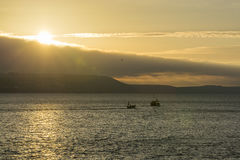 Fishing boats leaving Looe harbour at sunrise, Cornwall, UK Stock Photography