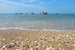 Fishing boats lie at anchor by sea, and the Beach and colorful shells royalty free stock image