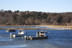 Fishing Boats and Lobster traps. Two fishing boats and a lobster barge resting on the partially frozen harbor. Taken at Cold Spring Harbor, Long Island, New York Stock Images