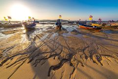 Fishing boats at low tide on the Chalong beach at sunrise time, Phuket, Thailand. Fishing boats at low tide on the Chalong beach at sunrise time, Phuket stock photos
