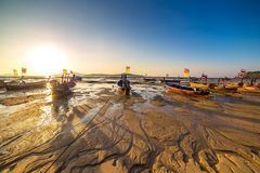 Fishing boats at low tide on the Chalong beach at sunrise time, Phuket, Thailand. Fishing boats at low tide on the Chalong beach at sunrise time, Phuket royalty free stock photos