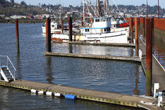 Fishing boats in a marina, Astoria OR. Fishing boats moored in a marina with  the Astoria city in the background Stock Photography