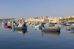 Fishing boats in Marsaxlokk bay. Traditional fishing boats at anchor in the calm waters of the Maltese fishing port of Marsaxlokk Royalty Free Stock Photos